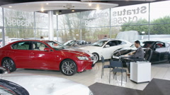 4K Time lapse of salesman & customers in busy car dealership.  Stock Footage