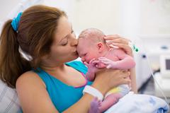 Young mother giving birth to a baby Stock Photos