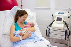 Young mother giving birth to a baby - stock photo