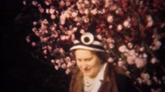 1948: Women wearing funny hat spring tree flower blossoms. - stock footage