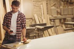 Happy carpenter on the phone in a dusty workshop Stock Photos