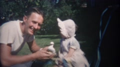 1948: Greaser style man entices uninterested baby with duck toy. Stock Footage