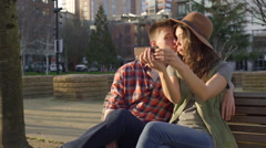 Couple Sit On A Bench And Take A Selfie, Her Boyfriend Kisses Her Cheek - stock footage