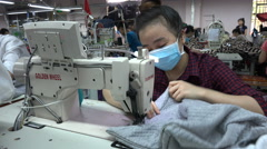 Production of jackets and other clothing, woman at work in garment factory Asia Stock Footage