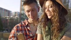 Cute Couple Sit On A Park Bench And Look Through Their Photos On A Smartphone Stock Footage