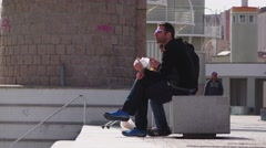 Two unidentified Spaniard sit and eat sandwich outside, stony bench at walkway Arkistovideo