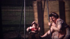 1948: Mother helping pink hood girl child on playground swingset. Stock Footage