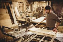 Carpenter working on his craft in a dusty workshop Stock Photos