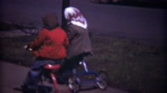 1948: Kids riding tricycles classic cars on neighborhood sidewalk. Stock Footage