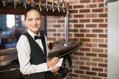 Barmaid taking orders on notepad - stock photo