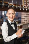 Barmaid taking orders on notepad - stock photo
