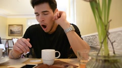 Young Man Drinking Coffee While Looking at Phone Stock Footage