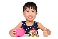 Stock Photo of Asian Little Chinese Girl Saving Money for Property Concept