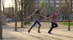 Fun Couple Run (Past Camera) In City Park On A Sunny Day Stock Footage