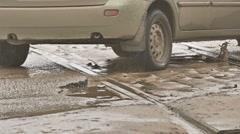 Bad asphalt road cars drive on dirt pits rain Stock Footage