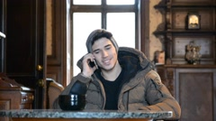 Handsome young man talking on telephone at home Stock Footage