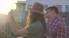 Attractive Couple Take Photo And Selfies From A Rooftop In A City At Sunset Stock Footage