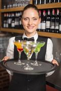 Barmaid holding plate with cocktails - stock photo