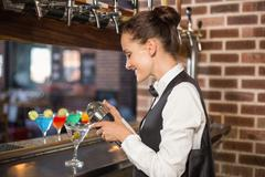 Barmaid pouring cocktail - stock photo