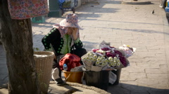 A Thai woman selling flowers in a pink hat holds her head in agony Stock Footage