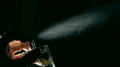 Spraying perfume against black background super slow motion dolly shot Stock Footage