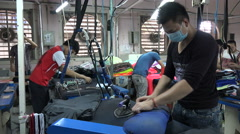 Worker ironing jackets in clothing factory, manual labor in Vietnam Stock Footage