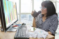 working woman with hot beverage cup in hand looking to computer monitor on wo - stock photo