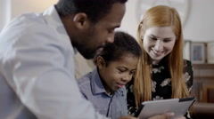 4K Happy mixed ethnicity family relaxing at home with computer tablet - stock footage