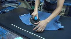 Closeup of a man ironing inside a blue shirt factory in Vietnam Stock Footage