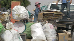 A busy recycling center with cardboard, trash, and bags on a scale Stock Footage