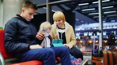 Mom and two kids waiting for a flight, children use smartphone and tablet Stock Footage