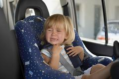 Young girl crying in her car seat - stock photo
