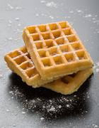 Sugary waffles on black table Stock Photos