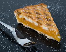 apple pie slice on black table with fork - stock photo