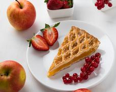 apple pie slice on white plate with fruits - stock photo