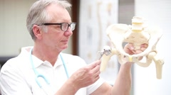Mature doctor demonstrating duohead hip endoprosthesis Stock Footage