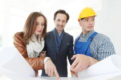 Worker shows house design plans - stock photo