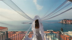Charming blond bride in long bridal veil standing on terrace with the Sveti Stock Footage