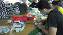 Garment factory, workers apply stickers to price tags, shirts for export - stock footage