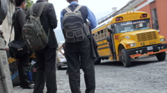 A school bus picks up students in the UNESCO heritage city of Antigua Stock Footage