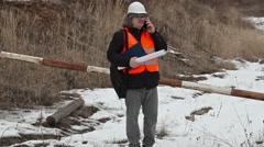 Engineer with documentation and smart phone in career - stock footage