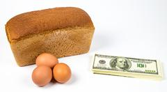 Expensive eggs, bread and money - stock photo