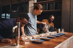 Modern roastery with baristas training to pour perfect coffee Stock Photos