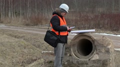 Engineer using tablet PC at the concrete pipes Stock Footage