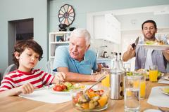Granddad talking to grandson while sitting at dining table Stock Photos