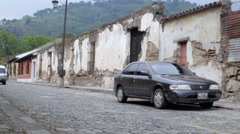 A mini bus drives down the cobble stone streets of Antigua, Guatemala Stock Footage
