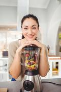 Portrait of cheerful woman preparing fruit juice - stock photo