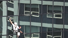 Window cleaner works on high rise building Stock Footage