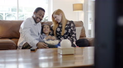 4K Happy mixed ethnicity family relaxing at home & watching TV Stock Footage