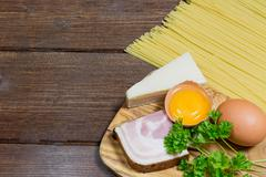 Spaghetti carbonara ingredients on the wooden desk - stock photo